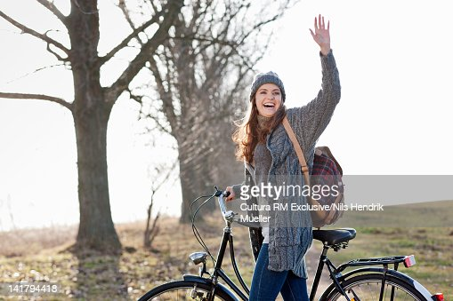 Smiling woman pushing bicycle outdoors