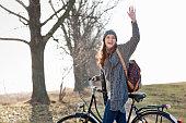 Smiling woman pushing bicycle outdoors