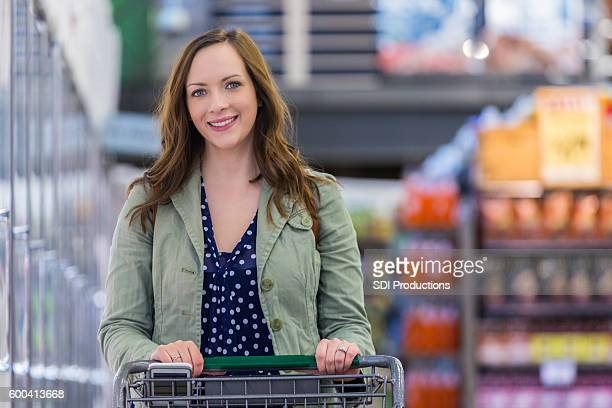 Smiling woman pushing grocery cart in a supermarket