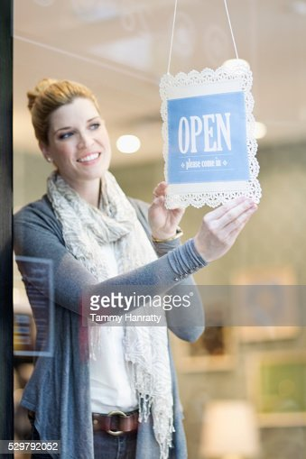 Smiling woman putting up open sign : Stock Photo