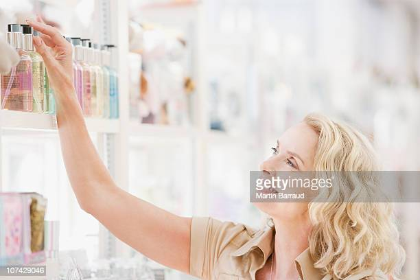 Souriant femme atteignant de parfum dans un magasin de gamme