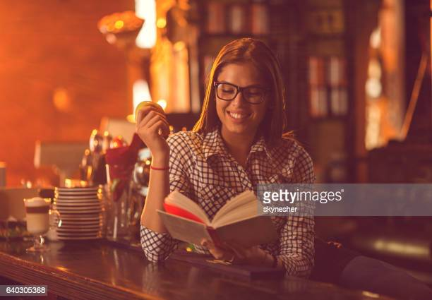 Smiling woman reading a book at bar counter.