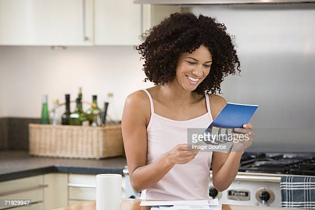 Smiling woman reading a brochure in kitchen