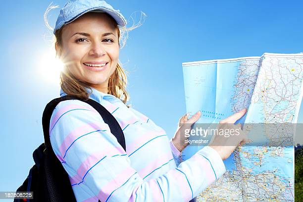 Smiling woman reading a tourist map.