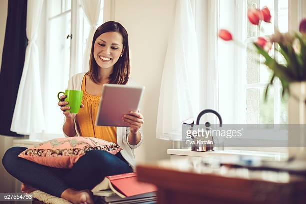 Smiling woman reading her tablet at home