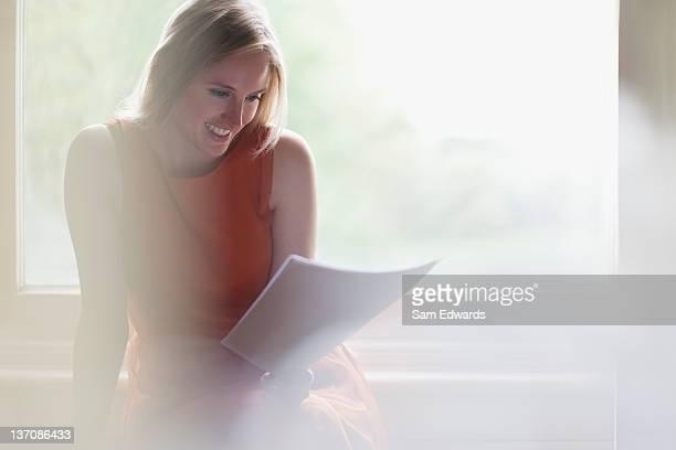 Lächelnde Frau liest Nachricht vor Fenster