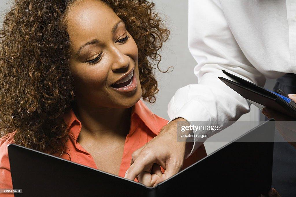 Smiling woman reading menu : Stock Photo