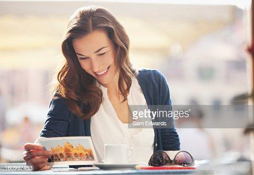Smiling woman reading postcard at sidewalk cafe