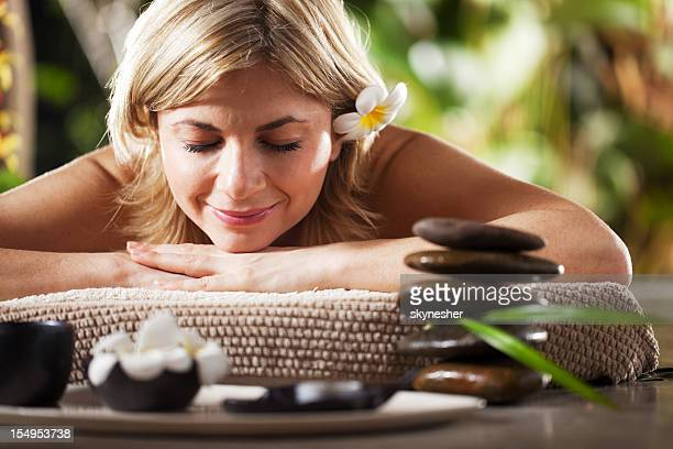 Smiling woman receiving massage therapy at spa