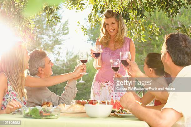 Smiling woman receiving toast outdoors