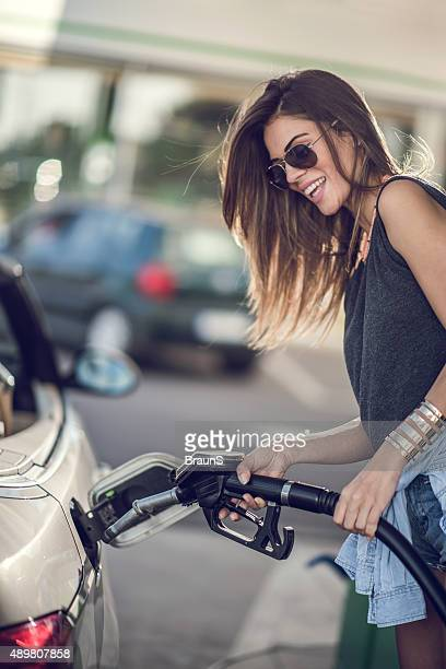 Smiling woman refueling her gas tank at fuel pump.