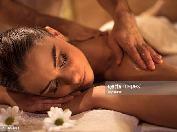 Smiling woman relaxing during back massage at spa.