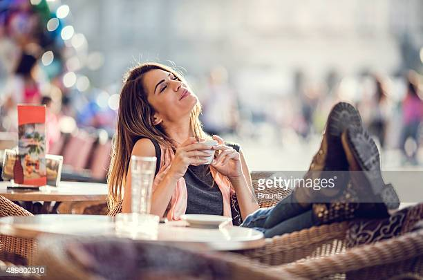 Smiling woman relaxing in a cafe with her eyes closed.