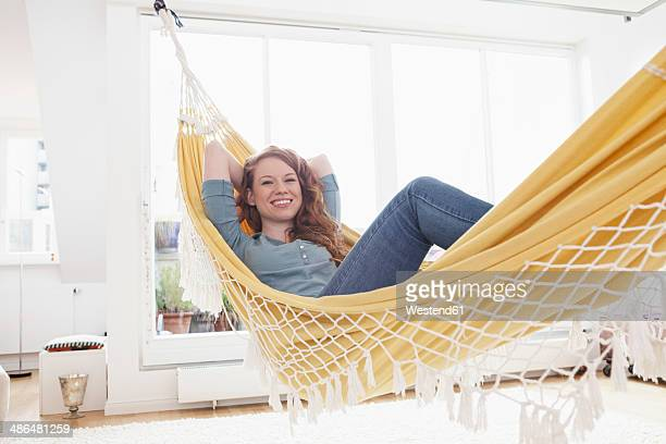 Smiling woman relaxing in a hammock in her apartment