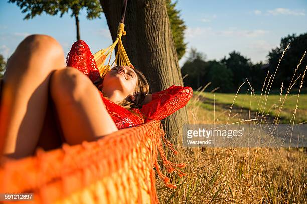 Smiling woman relaxing in a hammock in nature