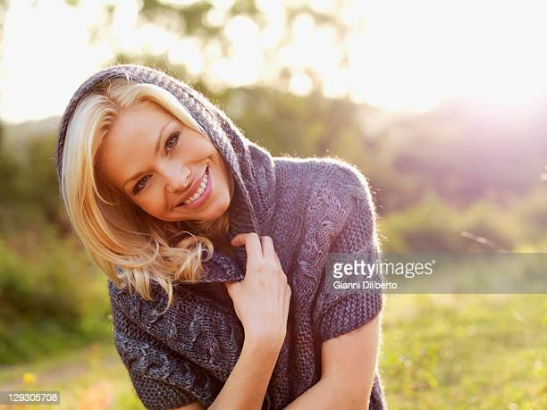 A smiling woman relaxing in the sun on an autumn day