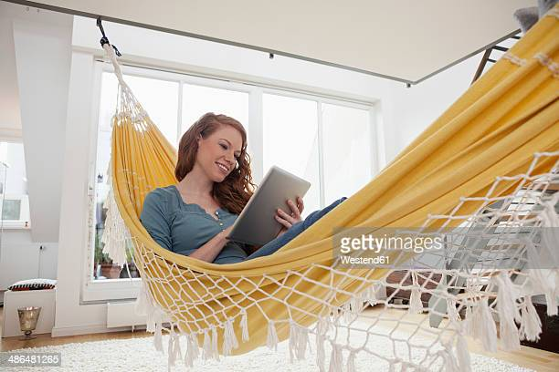 Smiling woman relaxing with tablet computer in a hammock in her apartment