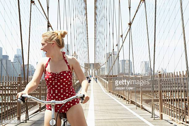 Smiling woman riding bicycle across urban bridge, New York, New York, United States