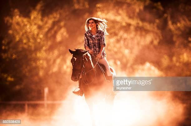 Cheval d'équitation femme souriante au coucher du soleil.