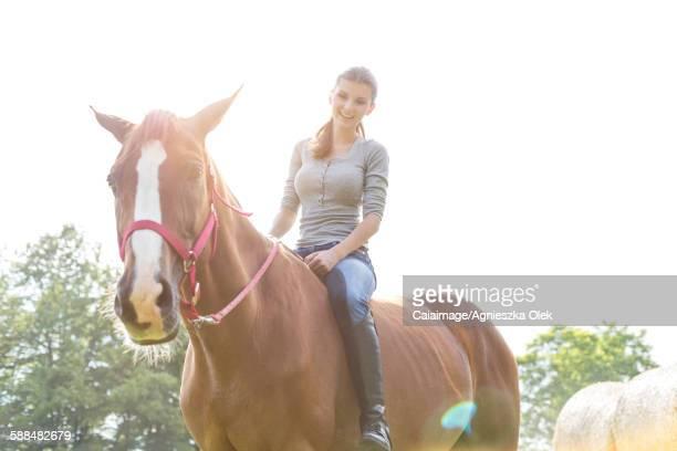 Smiling woman riding horse bareback