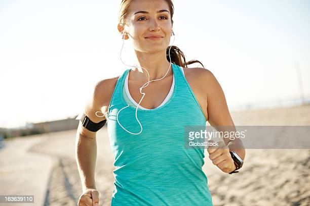 A smiling woman running while wearing earphones