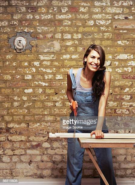 Smiling woman sawing wood
