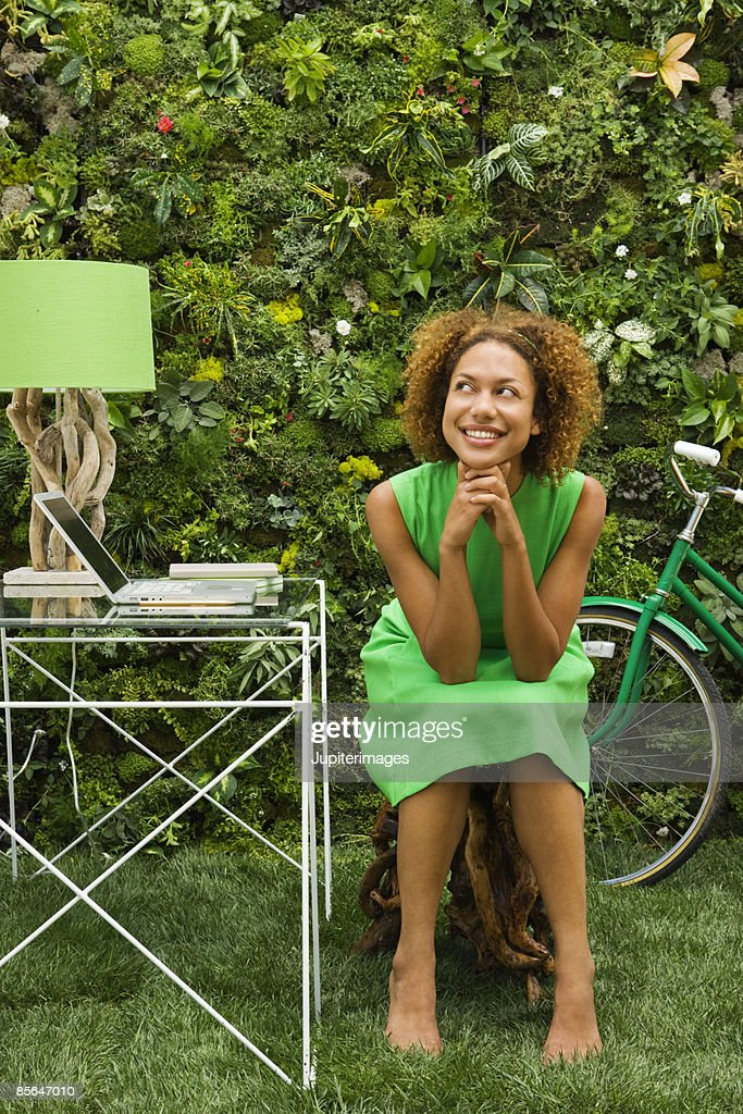 Smiling woman seated at desk : Stock Photo