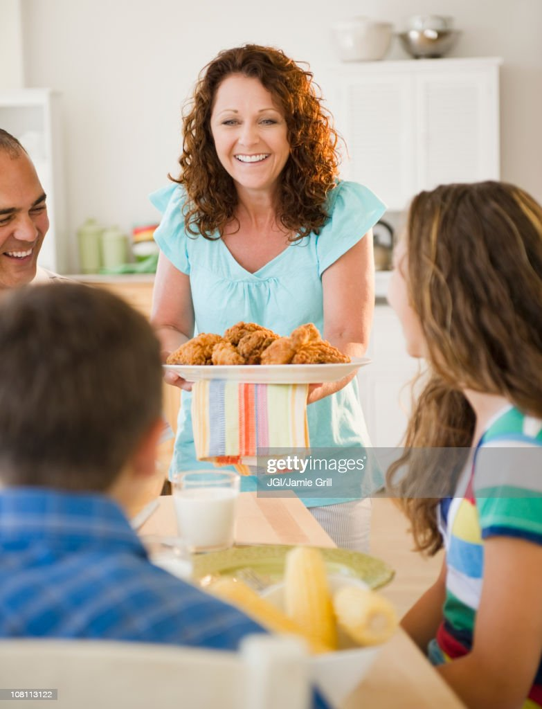 Smiling woman serving family dinner