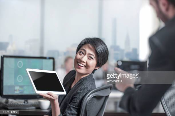 Smiling woman showing tablet to colleauge in city office