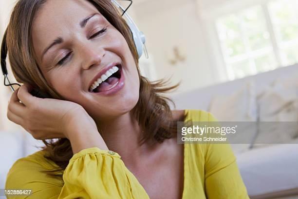 Smiling woman singing to headphones