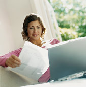 Smiling Woman Sits Behind her laptop Reading a Bill