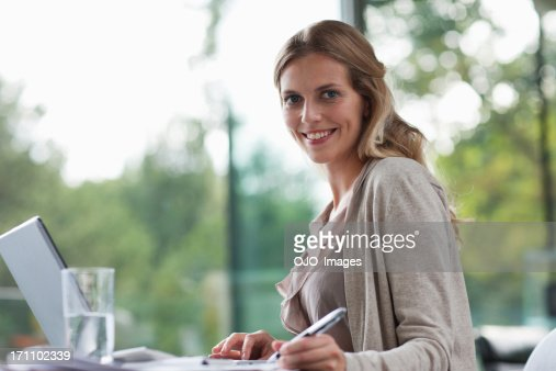 Smiling woman sitting at desk with paperwork : Stock Photo