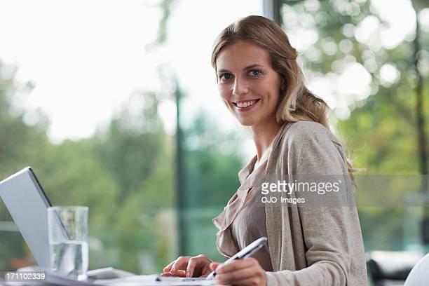 Femme souriante, assis au bureau avec les documents