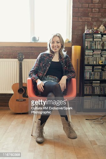 Smiling woman sitting in modern chair stock photo getty for Modern sitting chairs