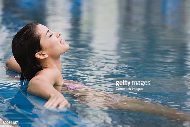Smiling woman sitting in swimming pool