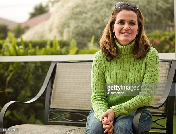 Donna sorridente seduto nel cortile di casa