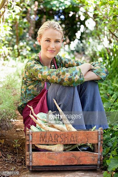 Smiling woman sitting near a crate of vegetables