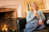 Smiling woman sitting on couch with fireplace