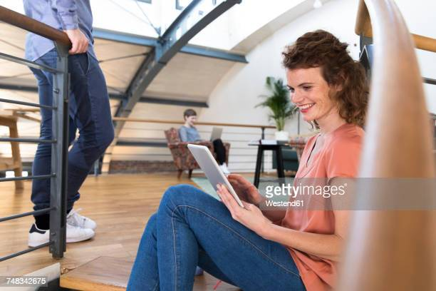 Smiling woman sitting on floor in modern office using tablet