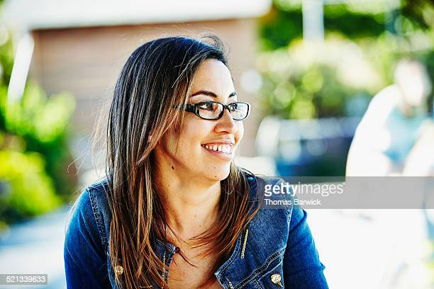 Smiling woman sitting on patio on summer afternoon