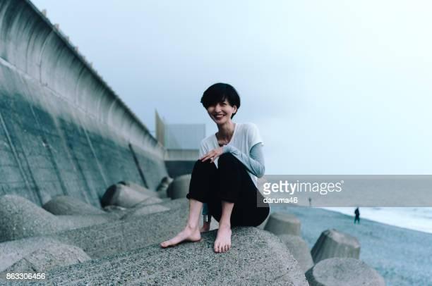 Smiling Woman Sitting on Tetrapod at Beach