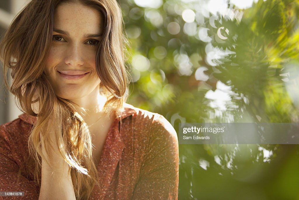 Smiling woman sitting outdoors : Stock Photo