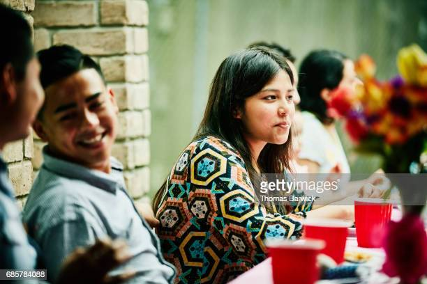 Smiling woman sitting with friends during family birthday party