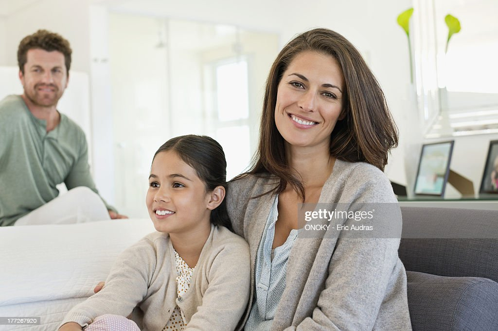 Smiling woman sitting with her daughter and her husband in the background : Stock Photo
