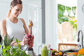 Smiling woman squeezing orange juice into blender with sliced watermelon and beet while preparing smoothie in kitchen