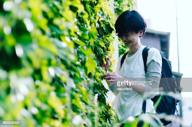 Smiling Woman Standing Against Ivy Wall