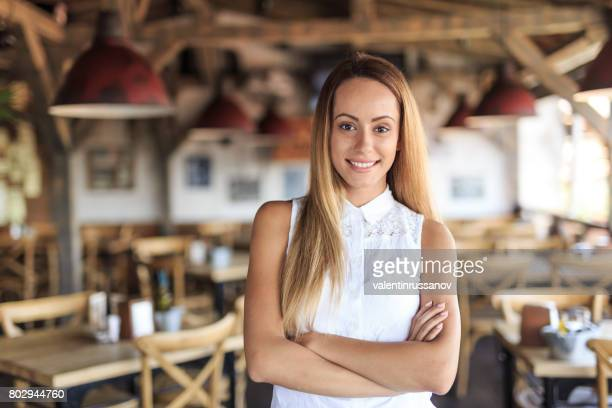 Smiling woman standing arms crossed in cafeteria