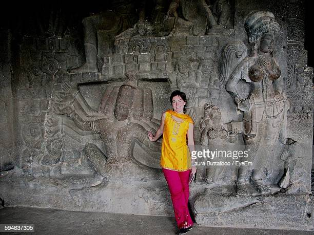 Smiling Woman Standing By Carvings At Ajanta Caves