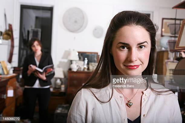 A smiling woman standing in an antiques shop