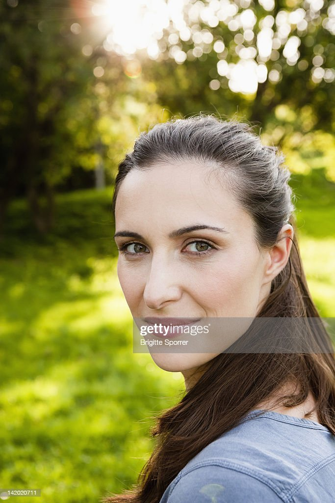 Smiling Woman Standing In Park Stock Photo | Getty Images